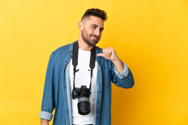 Фотограф человек изолирован на желтом фоне, гордый и самодовольный
