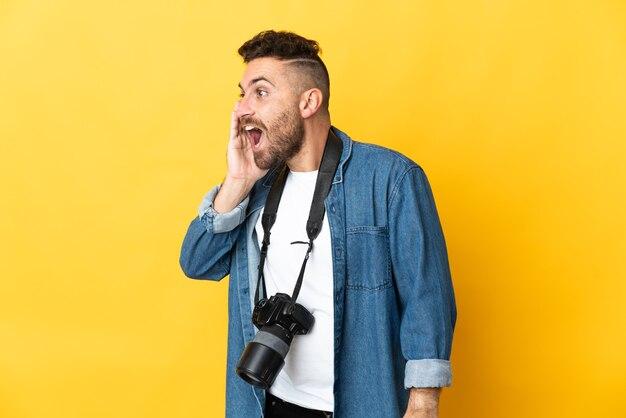 Фотограф человек изолирован на желтом фоне кричит с широко открытым ртом в сторону