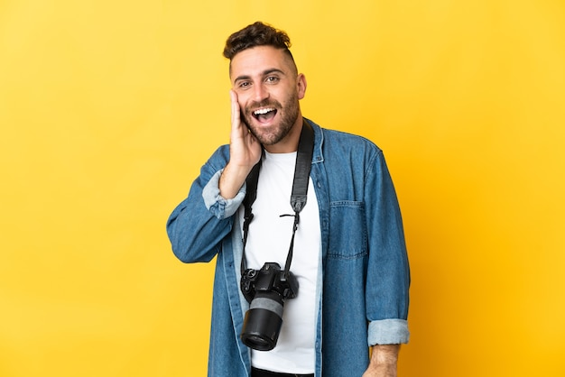 Фотограф человек изолирован на желтом фоне кричит с широко открытым ртом