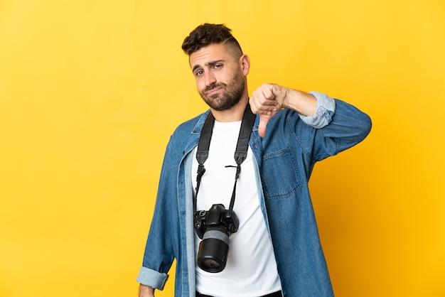 Фотограф человек изолирован на желтом фоне, показывая большой палец вниз с отрицательным выражением лица