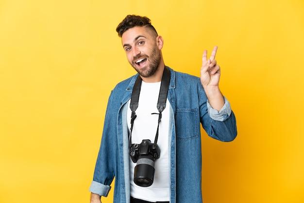 Фотограф человек изолирован на желтом фоне улыбается и показывает знак победы
