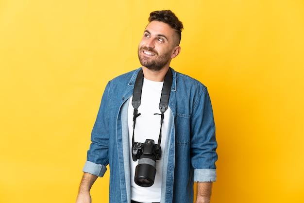 Фотограф человек изолирован на желтом фоне, думая об идее, глядя вверх