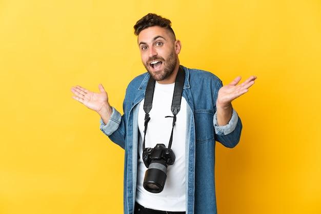 Фотограф человек изолирован на желтом фоне с шокированным выражением лица