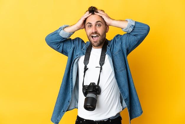 Фотограф человек изолирован на желтом фоне с выражением удивления