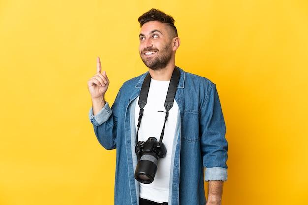 좋은 아이디어를 가리키는 노란색에 고립 된 사진 작가 남자