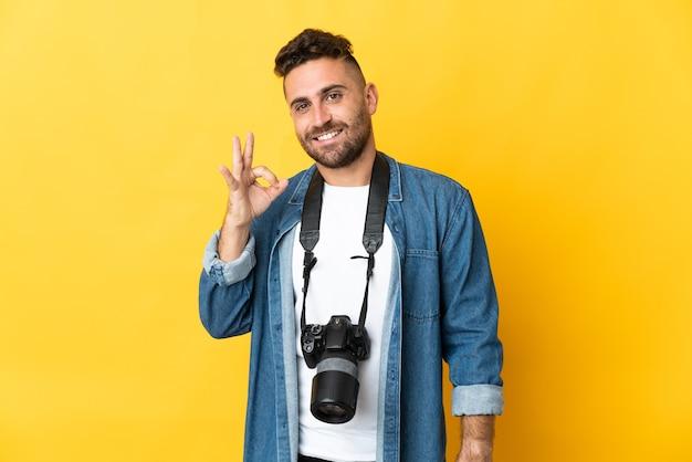 손가락으로 확인 표시를 보여주는 노란색에 고립 된 사진 작가 남자