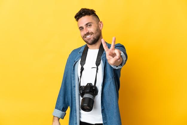 Фотограф человек изолирован на желтом, улыбаясь и показывая знак победы