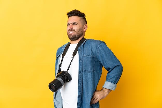 努力したために腰痛に苦しんで黄色に孤立した写真家の男