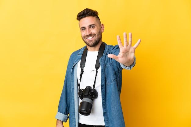 Фотограф человек изолирован на желтой стене, считая пять пальцами