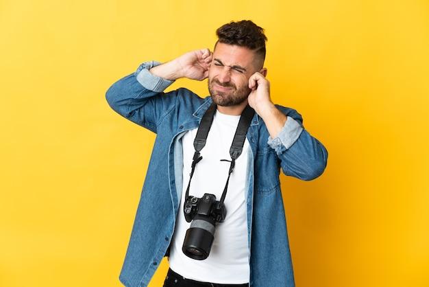 欲求不満と耳を覆っている黄色の壁に孤立した写真家の男