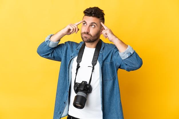 Фотограф человек изолирован на желтой стене, сомневаясь и думая