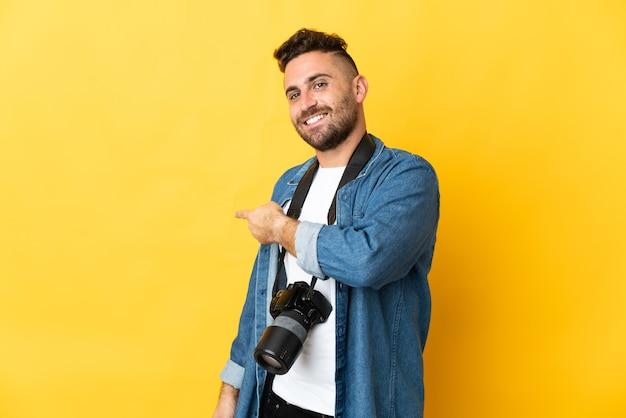 Фотограф человек изолирован на желтой стене, указывая назад