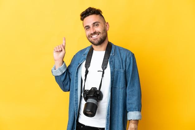 Фотограф человек изолирован на желтой стене показывает и поднимает палец в знак лучших