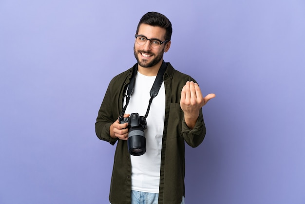 Photographer man over isolated purple inviting to come with hand.