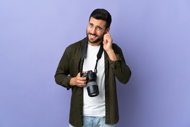 Photographer man over isolated purple wall frustrated and covering ears