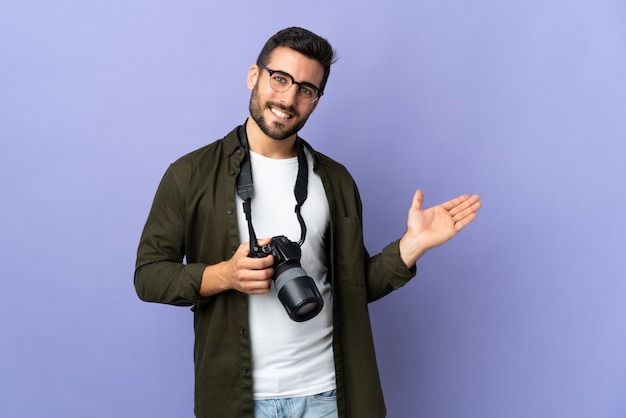 Photographer man over isolated purple wall presenting an idea while looking smiling towards
