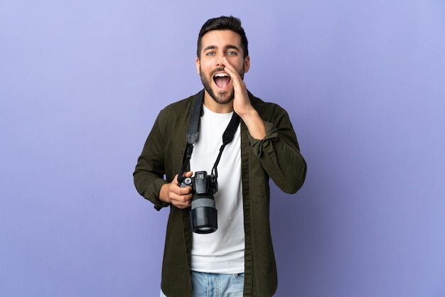 Photographer man over isolated purple wall shouting and announcing something