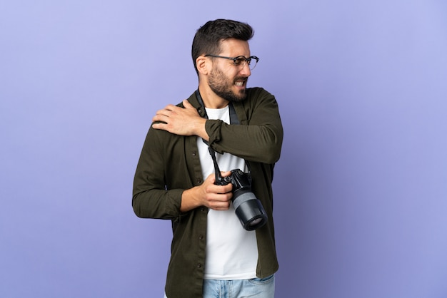 Photographer man over isolated purple wall suffering from pain in shoulder for having made an effort
