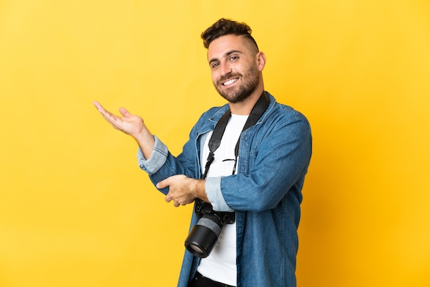 Photographer man isolated on yellow background extending hands to the side for inviting to come