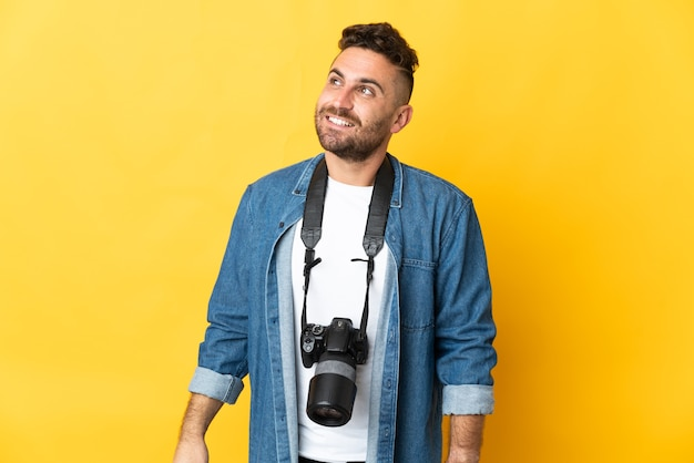 Photographer man isolated on yellow background thinking an idea while looking up