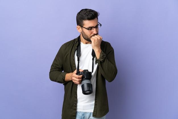 Фотограф человек на изолированном фиолетовом фоне сомневается