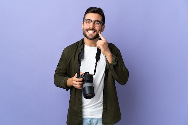 행복하고 즐거운 표정으로 고립 된 보라색 미소를 통해 사진 작가 남자