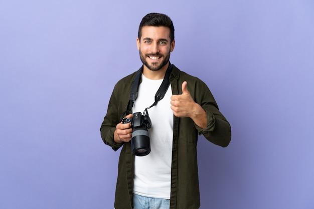 親指のジェスチャーを与える孤立した紫の壁を越えてカメラマン男