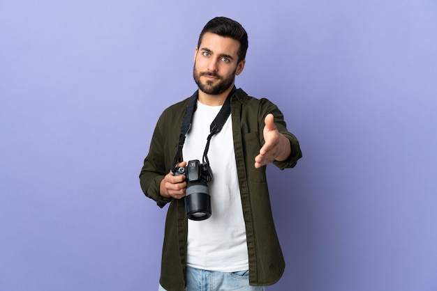 孤立した紫色の壁の上の写真家の男