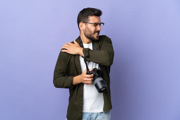 努力をしたための肩の痛みに苦しんでいる孤立した紫色の壁を越えて写真家男