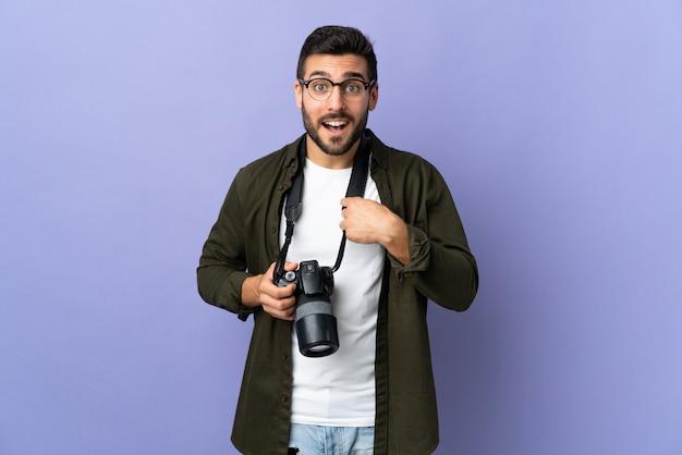 Человек фотографа над изолированной фиолетовой стеной с выражением лица сюрприза