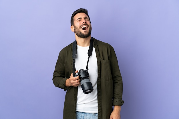 Photographer man over purple wall laughing