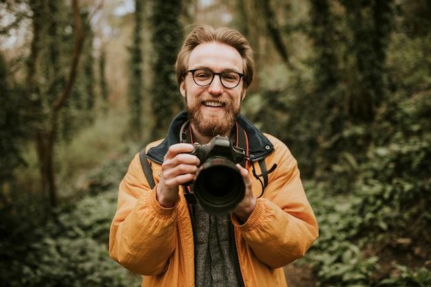 Фотограф человек улыбается, держа камеру в лесу