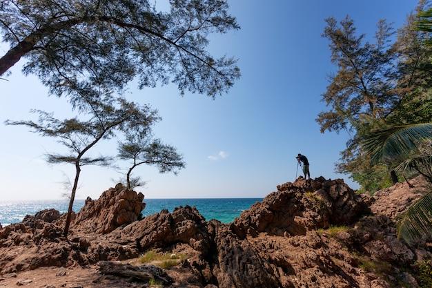 岩の崖の上に立っている写真家の男性は、撮影セッションの野生の海の風景を持っています。