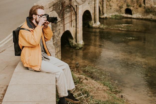 영국 코츠월드의 마을에서 사진을 찍고 있는 사진작가 남자