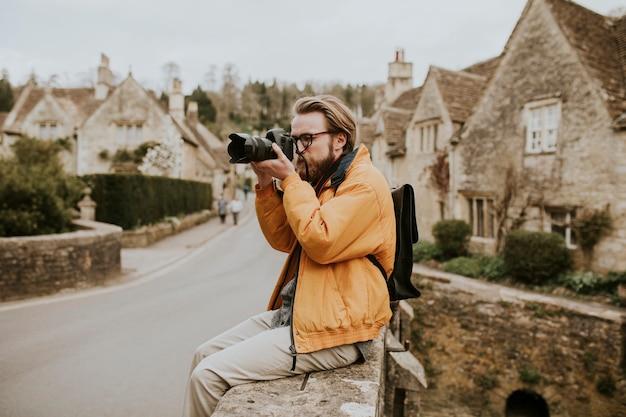 コッツウォルズ、イギリスの村で写真を撮る写真家の男