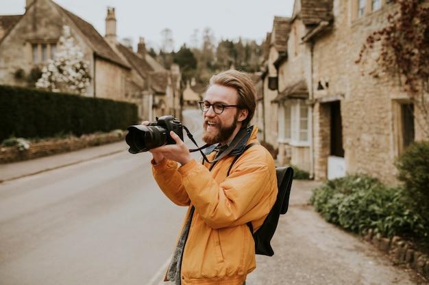 Fotografo uomo scattare foto nel villaggio in cotswolds, uk