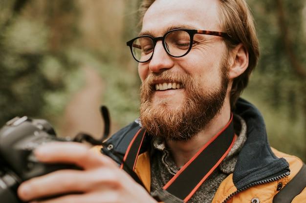 Фотограф человек просматривает свои фотографии на камеру на открытом воздухе