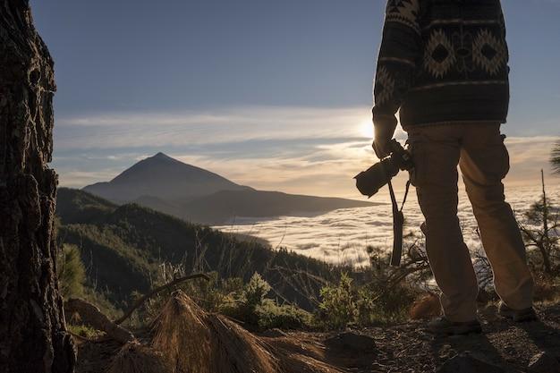 風光明媚な山の景色と空を賞賛するデジタル一眼レフカメラを持つ写真家の男。見事な山脈を眺めるハイカー。山頂の息を呑むような景色を眺めるカメラを持った観光客。