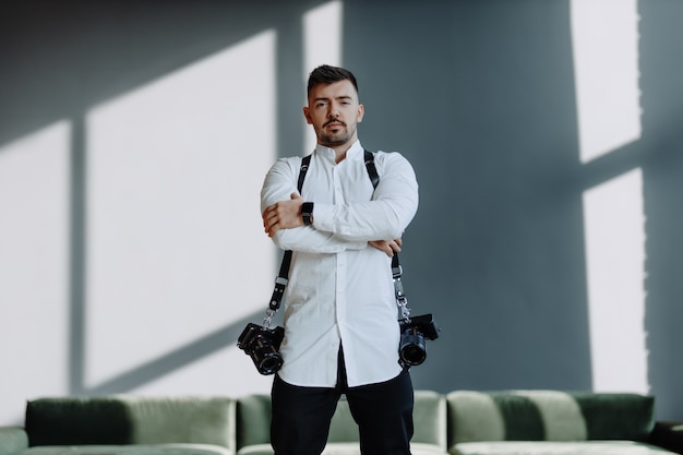 Photographer man with two cameras on a belts