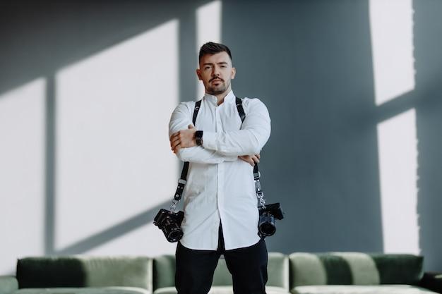 벨트에 두 개의 카메라와 사진 작가 남자