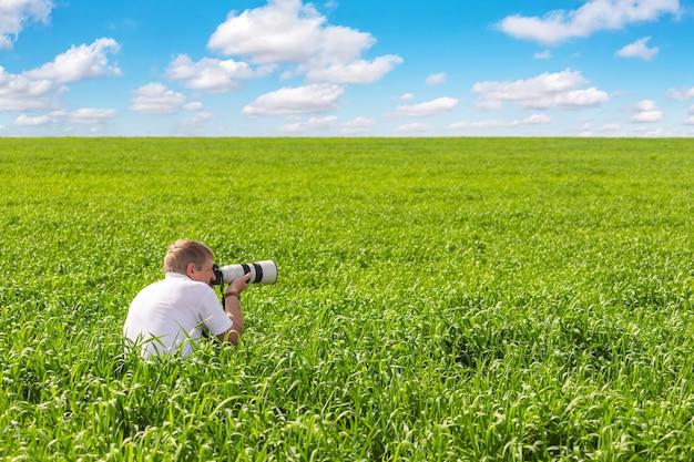 緑の野原の写真家が風景を撮影します