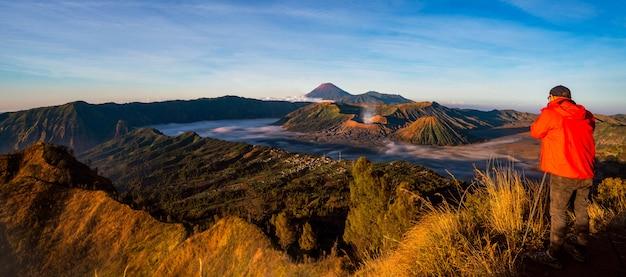 Фотограф на вершине горы, чтобы сфотографировать восход солнца для bromo vocano