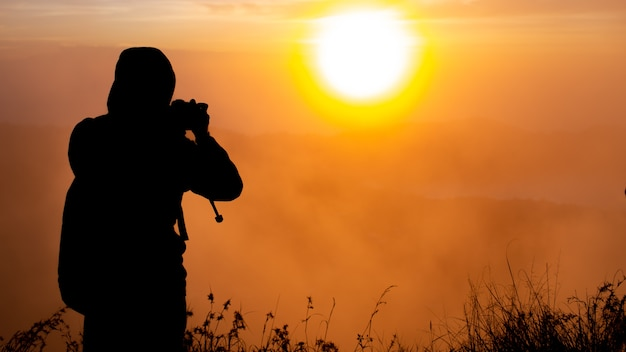 A photographer photographs the dawn of the sun on the volcano batur. bali indonesia