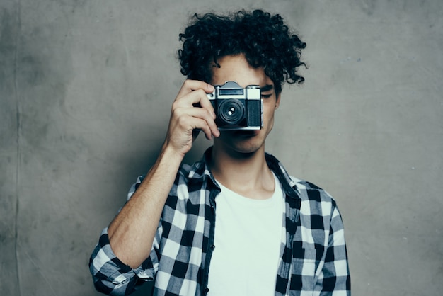 Photographer in a plaid shirt with a camera in his hand on a gray background in a hobby studio room Premium Photo