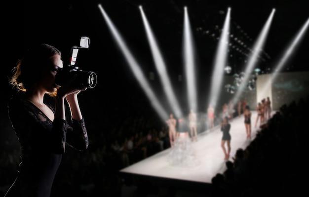 写真家のプレスウーマンがカメラを使って撮影するファッションウィークの写真どのモデルのスーパーモデルがランウェイキャットウォークを歩くかを示し、デザイナーブランドの新しいコレクション、背景のコピースペース