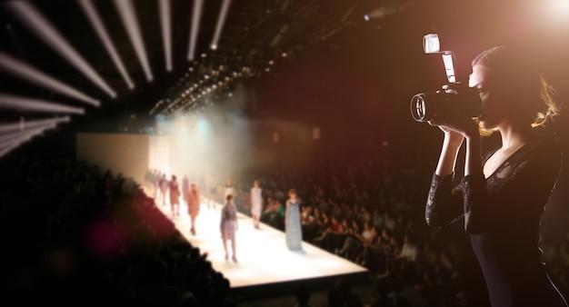 Фотограф press woman использует камеру для съемки фото с показа недели моды, на котором модель-супермодель идет по подиуму для новой коллекции дизайнерского бренда, пространство для копирования фона