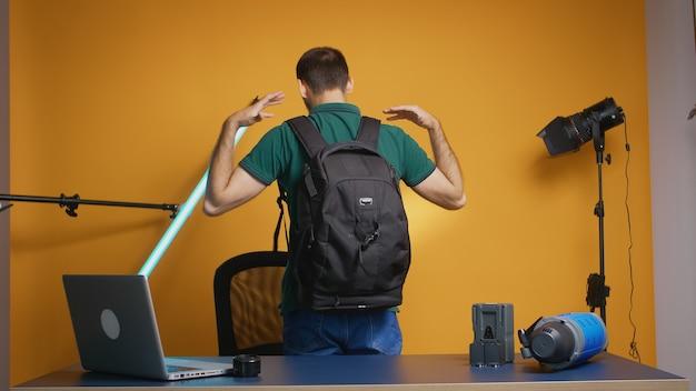 Фотограф записывает отзыв о рюкзаке для видеоблога и подписчиков. профессиональное студийное видео и фотооборудование для работы, звезда социальных сетей и влиятельный человек в фотостудии