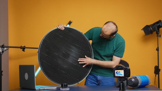 Photographer recording testimonial about silver beauty dish with honeycomb grid for vlog. professional studio video and photo equipment technology for work, photo studio social media star and influenc