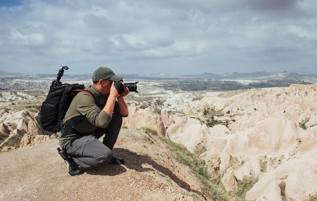 写真家の砂岩の崖と自然の風景を観察