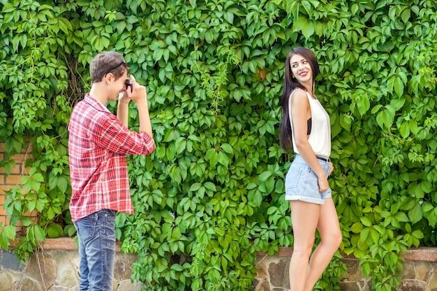 녹색 벽 근처에서 아름다운 갈색 머리 모델을 촬영하는 사진 작가